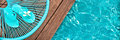 Turquoise blue garden chair and flip flops on on the edge of a swimming pool Royalty Free Stock Photo
