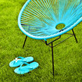 Turquoise blue garden chair and flip flops Royalty Free Stock Photo