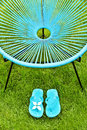 Turquoise blue garden chair and flip flops, green lawn Royalty Free Stock Photo