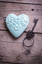 Turquoise decorative  heart and vintage key on aged wooden backg Royalty Free Stock Photo