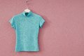 Turquoise female tee shirt is on coat hanger Royalty Free Stock Photos