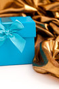 Turquoise gift box with elegant gold fabric tied a ribbon and bow arranged in saft luxurious folds over a white background Royalty Free Stock Photography