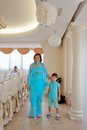 Turquoise holiday cheerful family in a blue suit on a background of snowy curtains Royalty Free Stock Photo