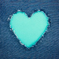 Turquoise vintage heart on blue denim fabric shape for copy space torn from jeans romantic love concept background Royalty Free Stock Photography