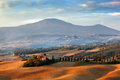 Tuscany landscape at sunrise. Tuscan farm house, cypress trees, hills. Royalty Free Stock Photo