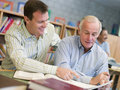 Tutor assisting mature student in library Royalty Free Stock Images