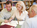 Tutor assisting mature student in library Royalty Free Stock Photo