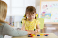 Tutor and preschooler kid playing with educational toys Royalty Free Stock Photo