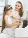 Tutor teaches little child to play piano master girl concept of music study and arts Royalty Free Stock Photos