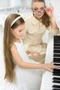 Tutor teaches little girl to play piano concept of music study and art Royalty Free Stock Photography