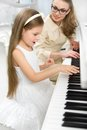 Tutor teaches little musician to play piano girl concept of music study and enjoyment Royalty Free Stock Images