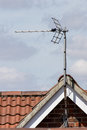 TV aerial on tiled roof top. Metal antenna on residential buildi Royalty Free Stock Photo