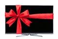 Tv as a present modern led with red christmas ribbon Royalty Free Stock Image
