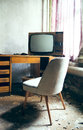 Tv from the old days an in an abandoned room with chair by window Royalty Free Stock Photos