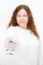 Tv remote control on foreground in hand with defocused woman white background Royalty Free Stock Images