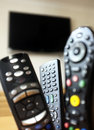 Tv remote controls group of with a at the background Stock Photography