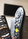 Tv remote controls group of with a at the background Stock Photo