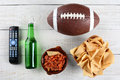 Tv remote salsa beer chips and football bottle bowl of with an american style on a rustic whitewashed wood surface horizontal Stock Photo