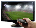 Tv screen with football match and hand remote control Royalty Free Stock Image