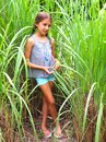 Tween Girl with Braids Poses In Tall Grass Royalty Free Stock Photo