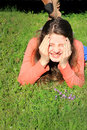 Tween thinking silly thoughts a pretty goofy girl lounging in the grass with in her head clasping face with hands shallow depth of Stock Images