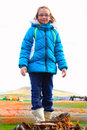 Tween in warm clothes a smile on a cute little blond year old girl wearing glasses and a blue winter hoody coat and boots standing Stock Image