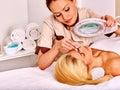Tweezing eyebrow by beautician woman getting indoor Stock Images