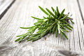Twigs of rosemary on wooden texture Royalty Free Stock Images