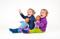 Twin babies laughing with dolls playing and Stock Photography