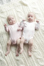 Twin baby girls lying on back on their blanket Stock Image