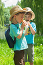 Twin boys ate ice cream three year old identical in cowboy hats in the park on one of the hats is partially visible motive of the Royalty Free Stock Image