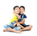 Twin brothers asian sitting on the floor and hug each other Royalty Free Stock Photos