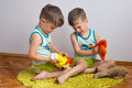 Twin brothers play with puppets three year old identical boys sit on the carpet and Stock Photography