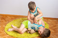 Twin brothers struggle on the floor three year old identical boys Stock Photo