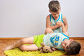 Twin brothers struggle on the floor three year old identical boys Royalty Free Stock Photography