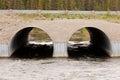 Twin culvert tunnel road bridge crossing wild river Royalty Free Stock Photo