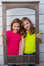 Twin sister girls posing with aged wooden border frame on white wall Stock Photos