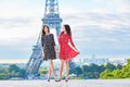 Twin sisters in front of the Eiffel tower in Paris, France Royalty Free Stock Photo