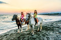 Twin sisters riding horses in the  sunset by the sea on the isla Royalty Free Stock Photo