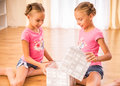Twin sisters twins open a paper box sitting on the floor Stock Image