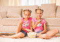 Twin sisters twins are watching tv and eating popcorn sitting on the floor Stock Photos
