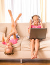 Twin sisters young twins are using laptop headphone and smartphone sitting on the couch Stock Images
