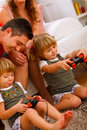 Twins daughters playing on console at home Royalty Free Stock Images