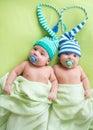 Twins infant boys babies weared in striped hats tied by heart.