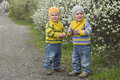 Twins near the blossoming shrubs identical on gravel road season spring boys dressed in same stripy jumper and hats in Royalty Free Stock Image