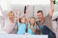Twins and parents raising arms while watching television sitting on a carpet Stock Images
