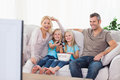 Twins and parents watching television sitting on a couch Stock Photo