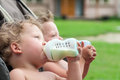 Twins suck a bottle with milk Royalty Free Stock Photo