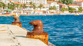 Two abandoned iron rusty piers in a mediterranean harbor mediterrean with village as background Stock Photo
