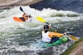 Two active kayakers are rolling and surfing in rough water Royalty Free Stock Photography